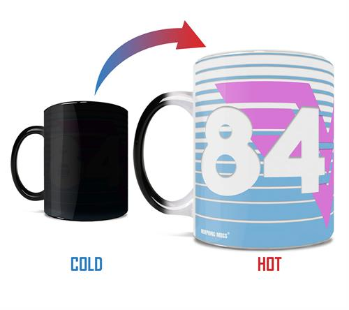 "Are you ready for Wonder Woman 1984? So are we! This 11 oz Morphing Mugs Color Changing Mug features the Amazonian warrior's iconic logo in a neon pink hue and ""84"" in a large print on the two sides of the mug."