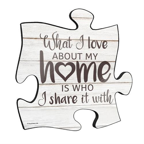 "What I love about my home is who I share it with. This unique 12"" x 12"" wooden puzzle piece wall art is perfect for wherever you call home. This rustic style wall décor has a realistic white wood printed design with the cute quote displayed across it."