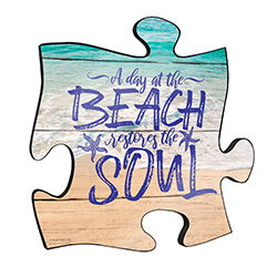 "Reminisce on your favorite beach trips with this 12"" x 12"" puzzle piece wall art. Printed on this unique home décor is the quote ""A day at the beach restores the soul,"" along with a scenic design of waves crashing onto the sandy beach."