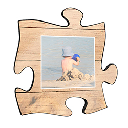 "Reminisce on your favorite beach trips with this 12"" x 12"" puzzle piece wall art. Printed onto this unique home décor is your favorite photo and a design of the sand framing the image."