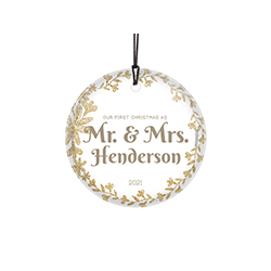 "This 3.5"" glass ornament features a white background with gold floral accents, the phrase ""Our First Christmas as Mrs. And Mrs."" and areas to customize the item with your wedding year and last name."