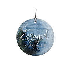 Congratulations! You're celebrating your first Christmas engaged! This frosty image of sprigs of green and an icy blue background, featuring your names and year, is fused directly and permanently into the glass for a light-catching, long-lasting keepsake.