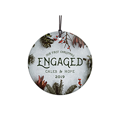 Congratulations! You're celebrating your first Christmas engaged! This frosty image with winter greens and cranberries, featuring your names and year, is fused directly and permanently into the glass for a light-catching, long-lasting keepsake.