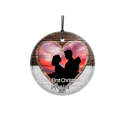 "Celebrate your marriage for years to come with this glass ornament. Featuring a faded wood design, this 3.5"" circular glass ornament features the phrase ""Our First Christmas as Mr. and Mrs."", your wedding year and a space to upload your image."
