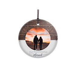 "Let the wedding bells continue ringing for years to come! Featuring a rustic wood design, this 3.5"" circular glass ornament features the phrase ""Our First Christmas Married"", your wedding year and a cirular-shaped space to upload your image."