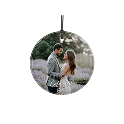 "This 3.5"" circular glass ornament features the phrase ""Our First Christmas Engaged"" and your engagement year. Add your favorite photo as the background of this minimalistic yet elegant design."